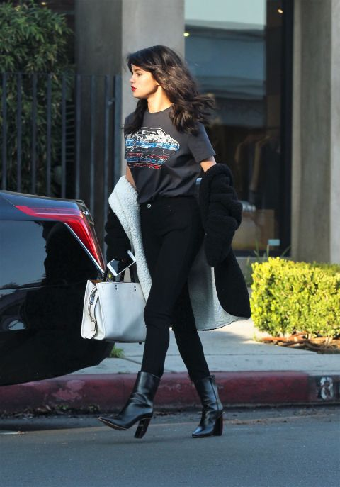 In Coach's Pre-Spring car t-shirt and carrying a Coach rogue bag while out in Los Angeles.