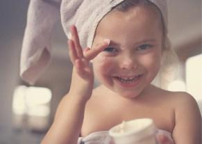 child putting on skin care cream