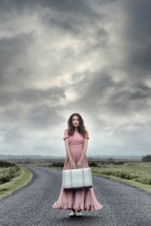 a woman in a pink dress is standing on a road with a white suitcase