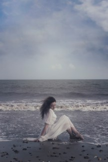 a woman in a white dress is sitting in the sea