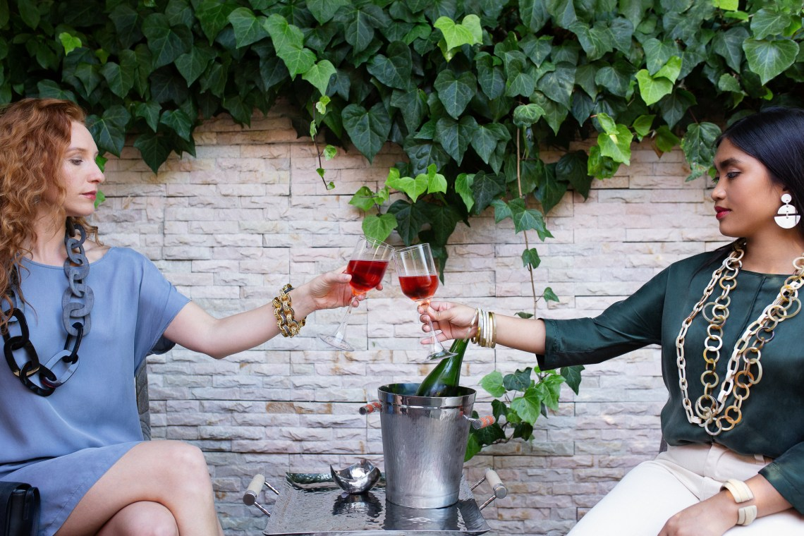 Cheers, two women enjoying rose in the garden wearing Vivo jewelry. Photography by Ella Sophie