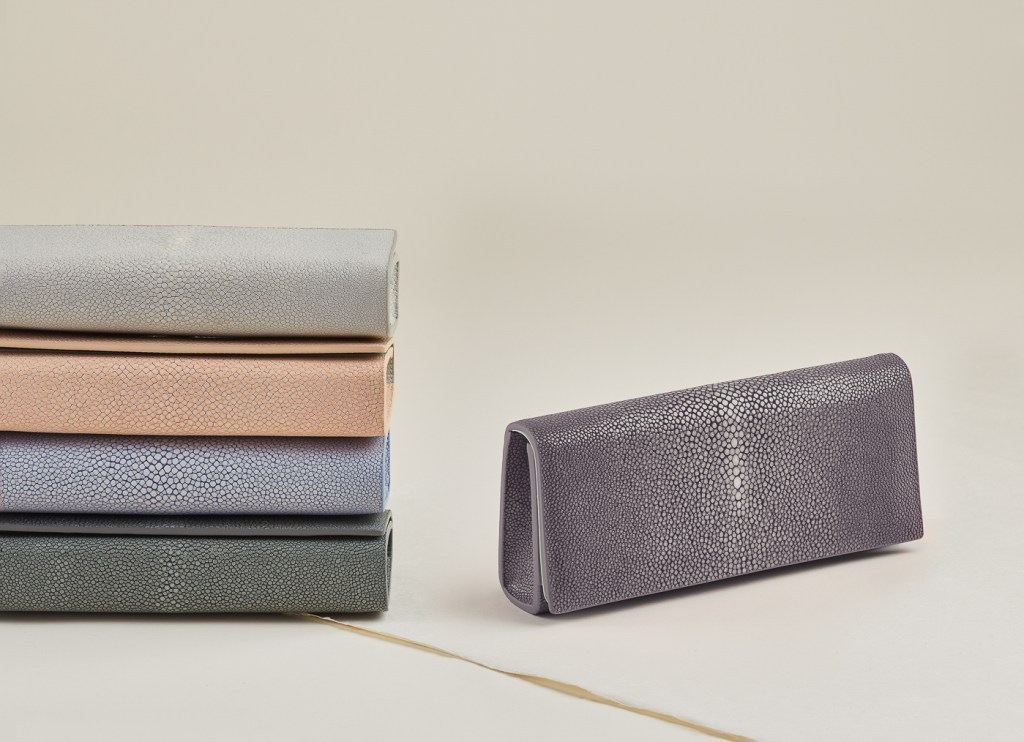 Still life of stack of shagreen clutch wallets. Product advertising photography by Ella Sophie