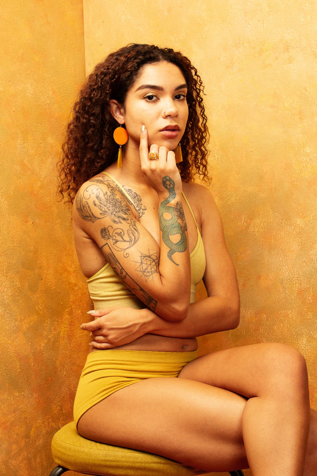 Tattooed model in gold themed shoot for Jewelry. By Oakland jewelry photographer Ella Sophie