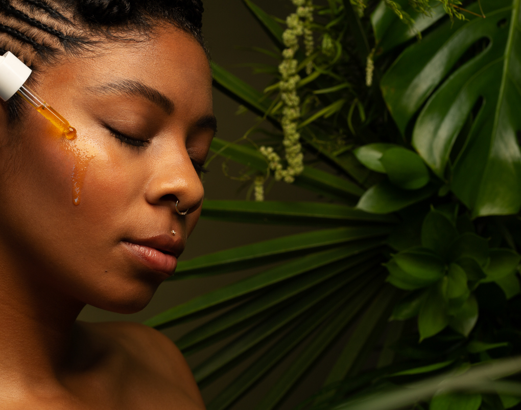 Portrait of black woman with glowing skin and cbd face serum with leaves by Ella Sophie Photographer