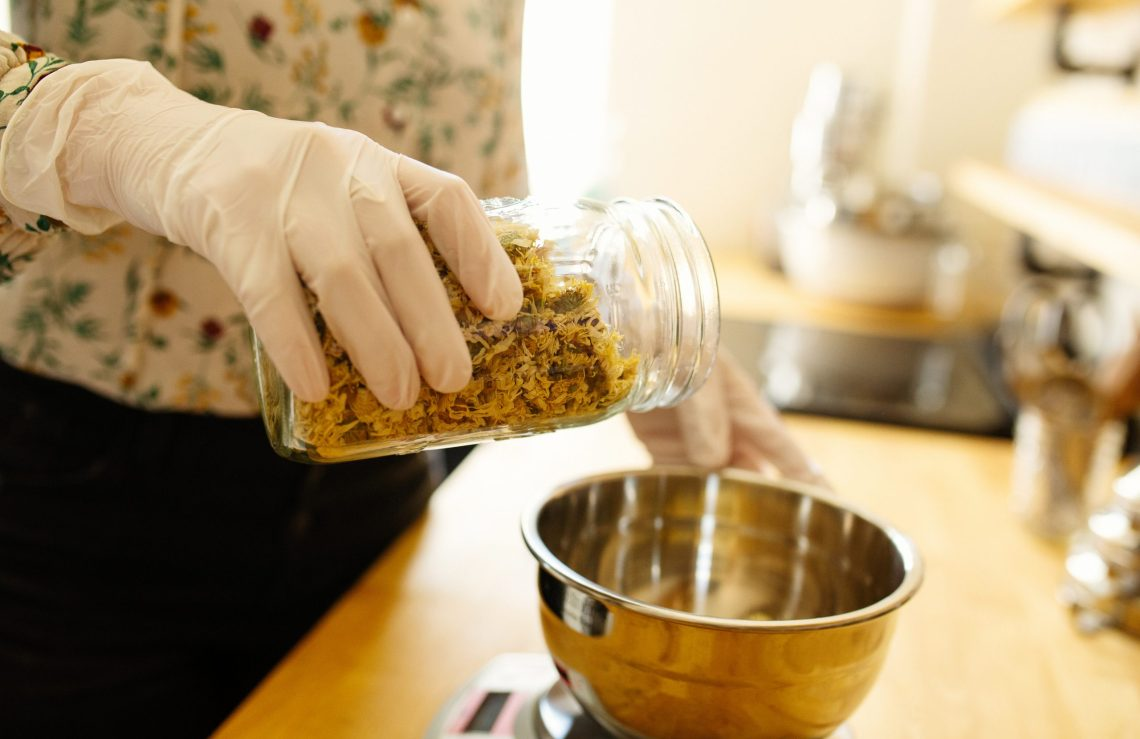 Close up detail shot showing gloved hand, metal bowl and glass jar with herbs. Traditional Chinese herbal medicine. Marketing photography byEllaSophie, California commercial photographer.