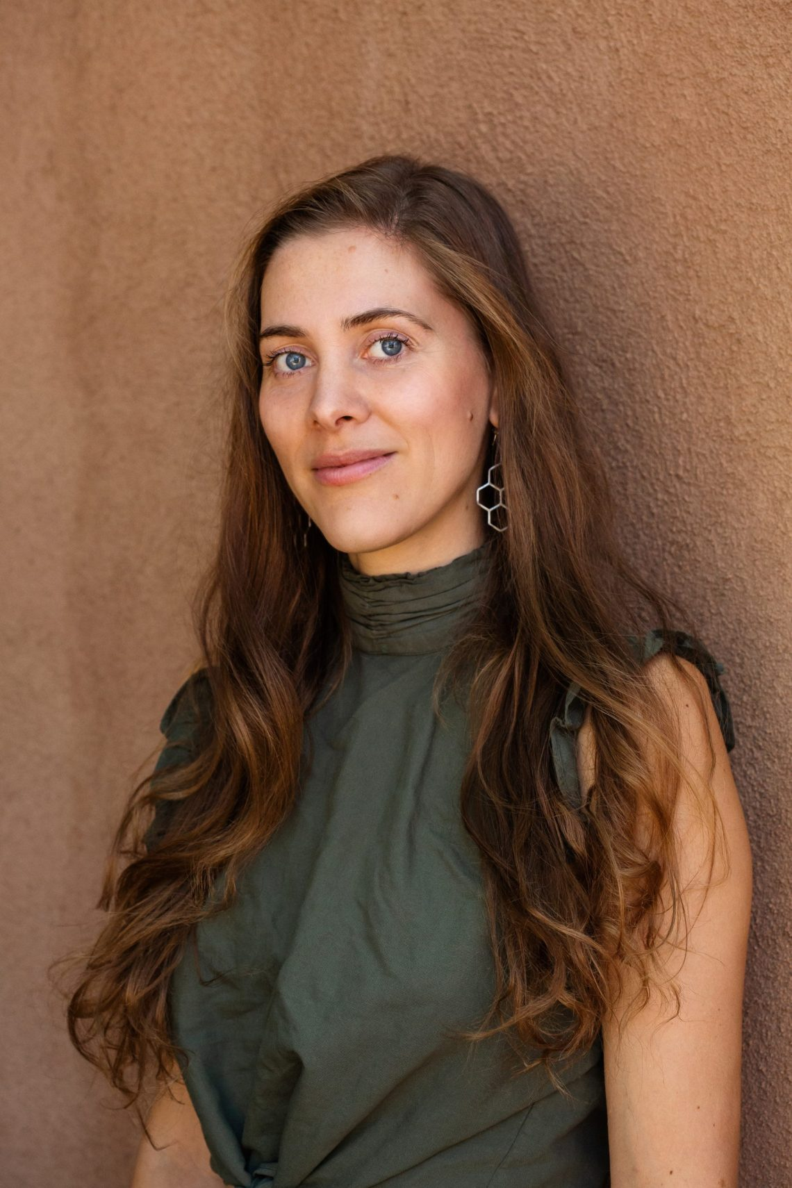 Neutral earth toned portrait photography by Oakland photographerEllaSophie. Portrait of Dr. Clara Wetmore in Taos NM wearing green shirt in front of brown adobe style wall.