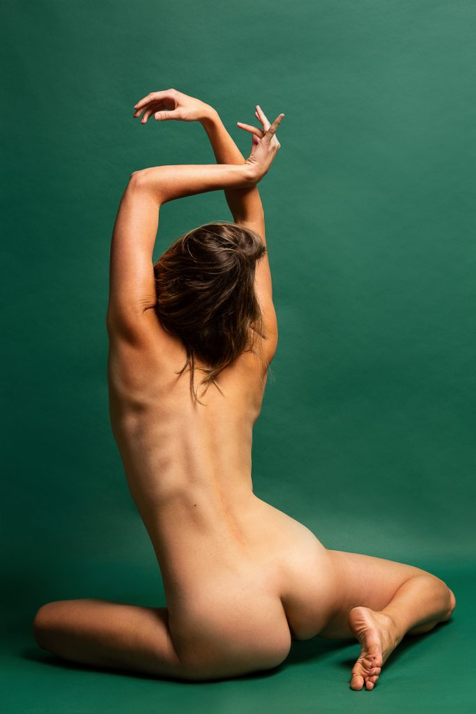 Implied nude artistic personal portrait, woman in photography studio posing against green background with natural lighting. Portrait by Ella Sophie photographer in Oakland CA.