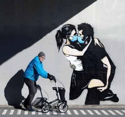 graffiti por el coronavirus pareja besandose con mascarillas
