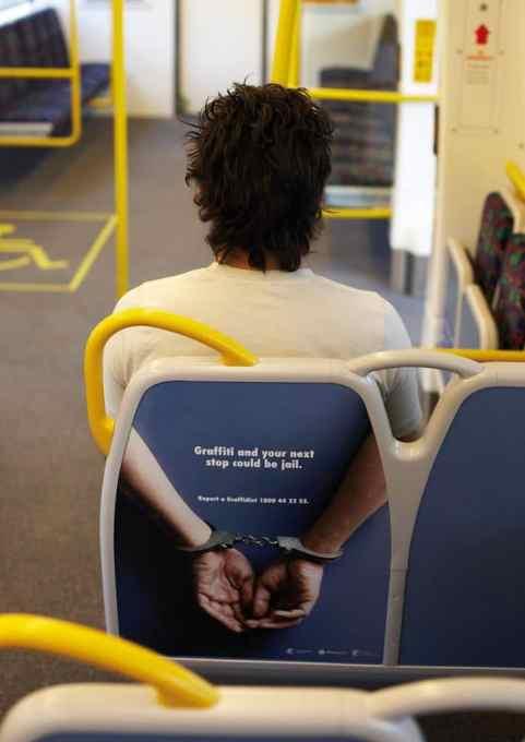 Hombre sentado en asiento de autobus público con esposas