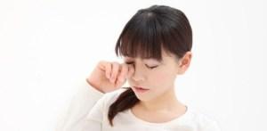花粉症の目をこする女性