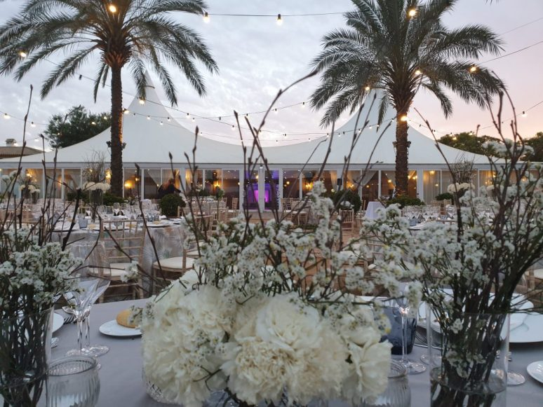 Salón de boda al aire libre con enfoque de mesa nupcial.