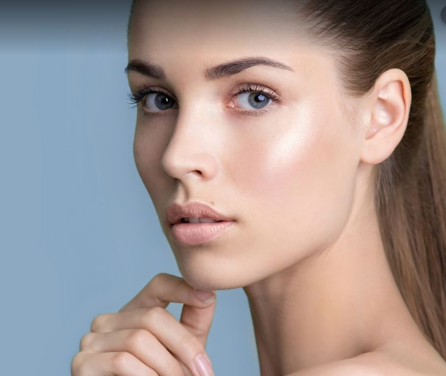 face model woman looking at skin with clear skin blue background ellemes medical spa atlanta