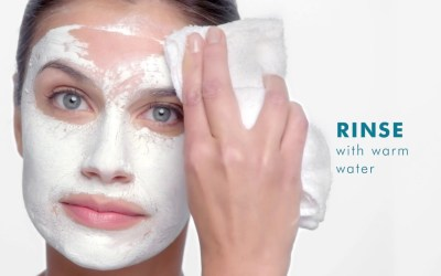 woman rinsing skincare from face