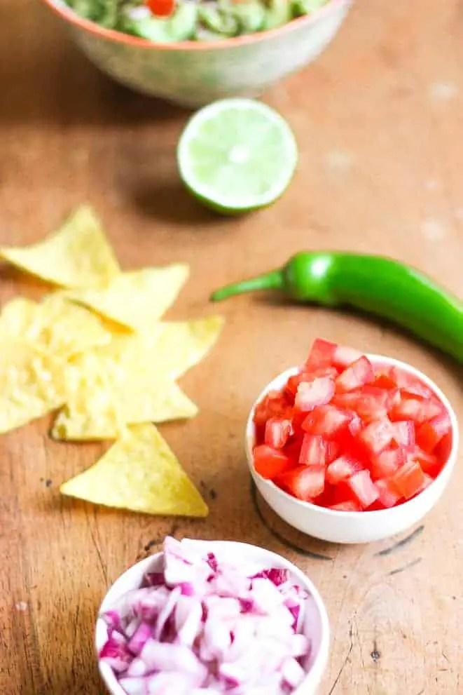 Guacamole préparé avec du piment vert, tomates, oignons rouge et tortillas