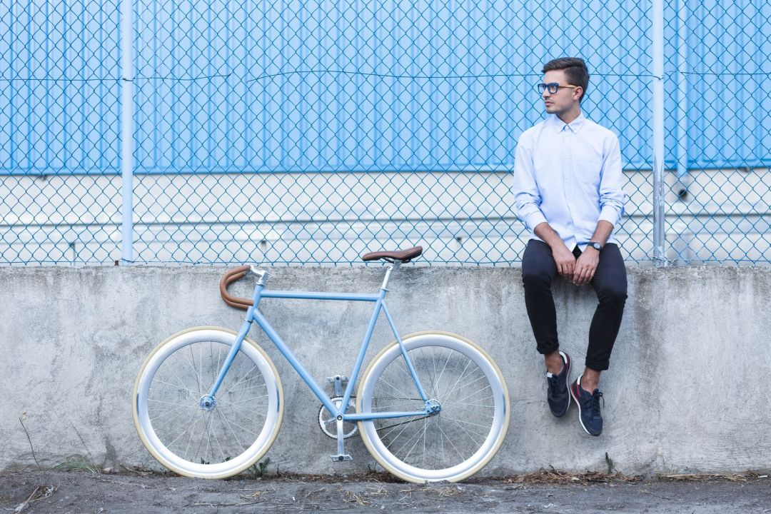Sitting young hipster and trendy city bike