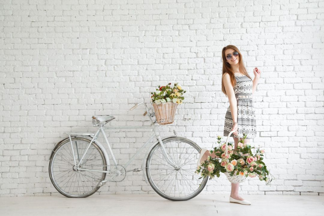 Portrait of a happy beautiful young girl with vintage bicycle and flowers