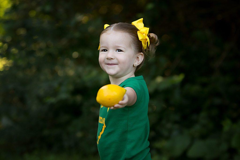 Two year old girl holding lemon