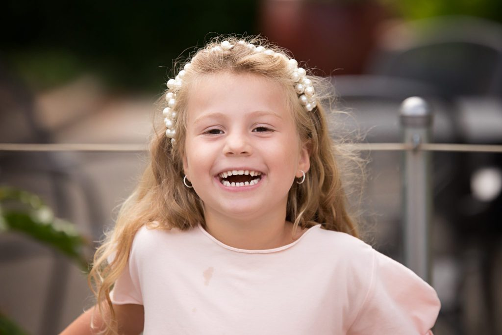 Little girl smiles while playing during her photo session