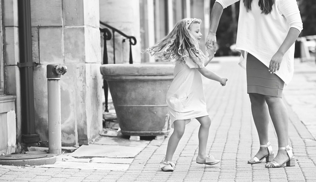 mom helps her daughter spin during photo session