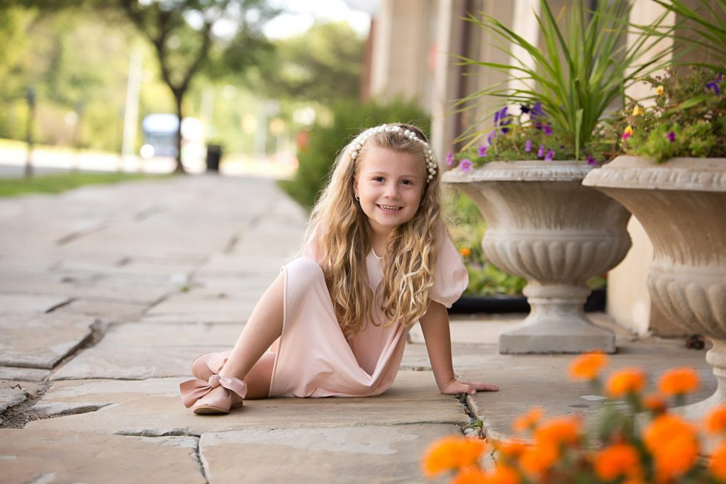 little girl posing during her photo shoot on flagstone sidewalk surrounded by potted plants