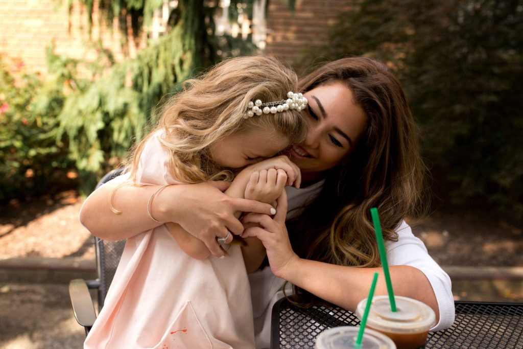 little girl and her mom share cuddles and laughs while drinking starbucks