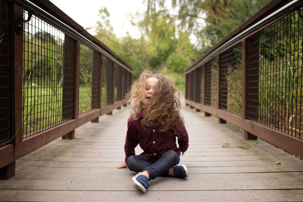 three year old boy on a bridge with long hair flying