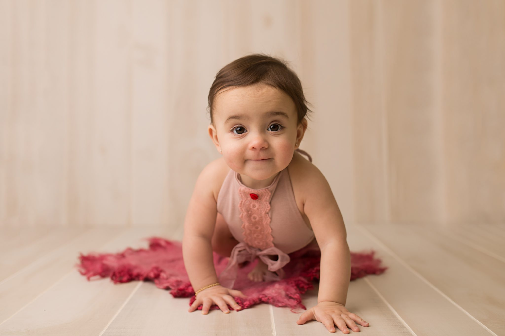 9 month old in-studio sitter session in a mauve romper