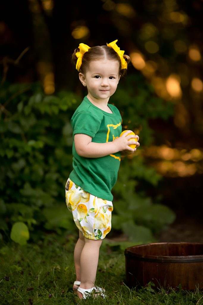 two year old girl in lemon print shorts holding a lemon