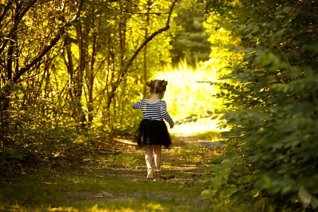 little girl in black and white striped dress running through a path in the woods