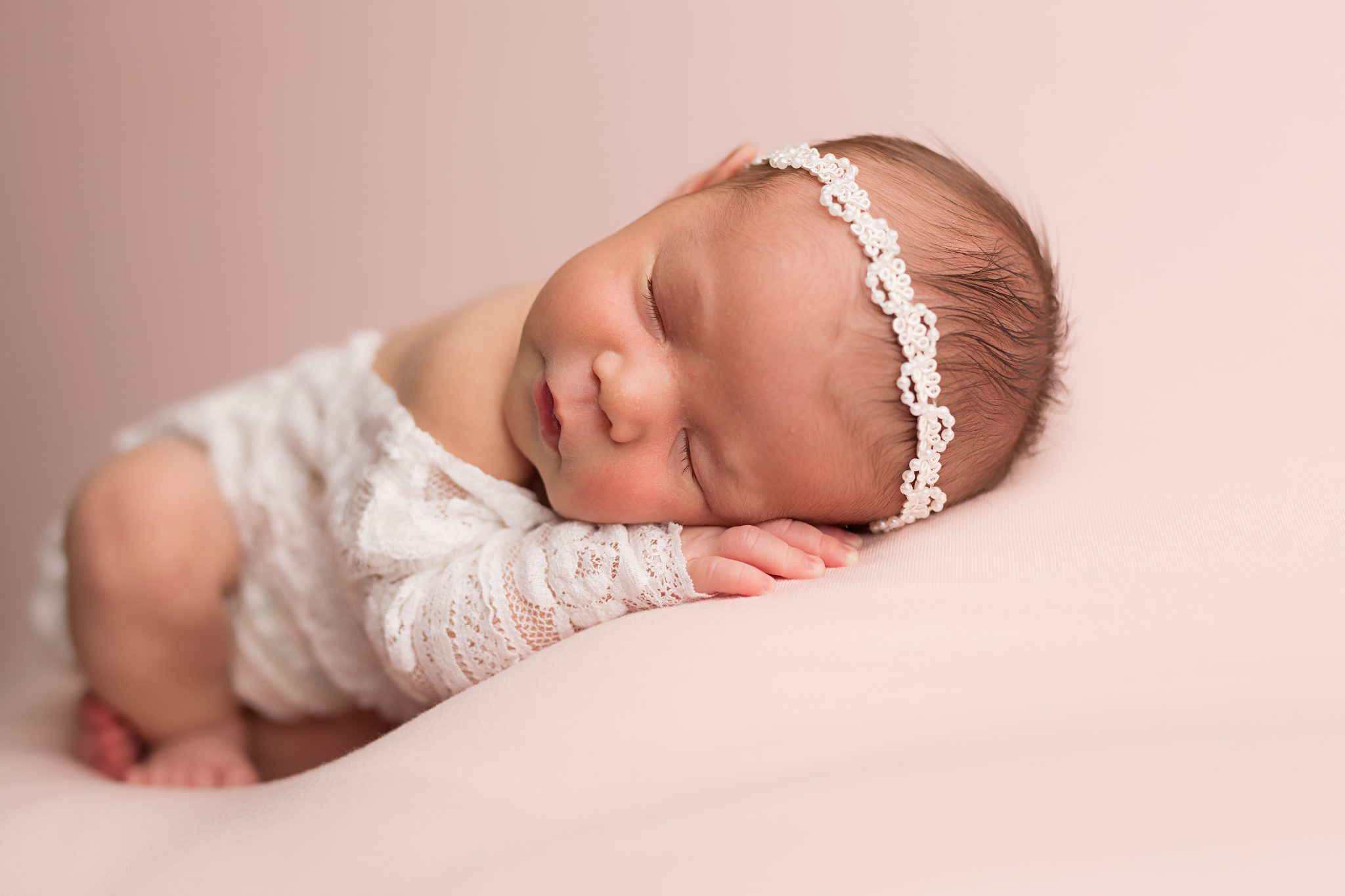 newborn baby girl in lace romper laying on pink packground