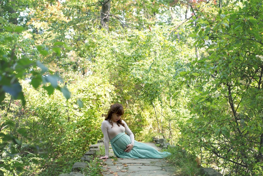 pregnant woman sitting on stone bridge in the trees