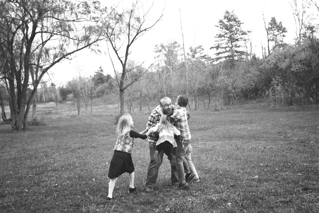 kids running and jumping into their father's arms in an open field