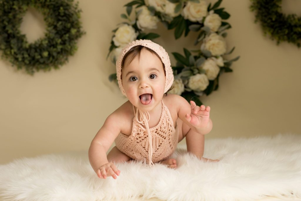 one year old girl in peach romper and bonnet with floral wreaths behind her
