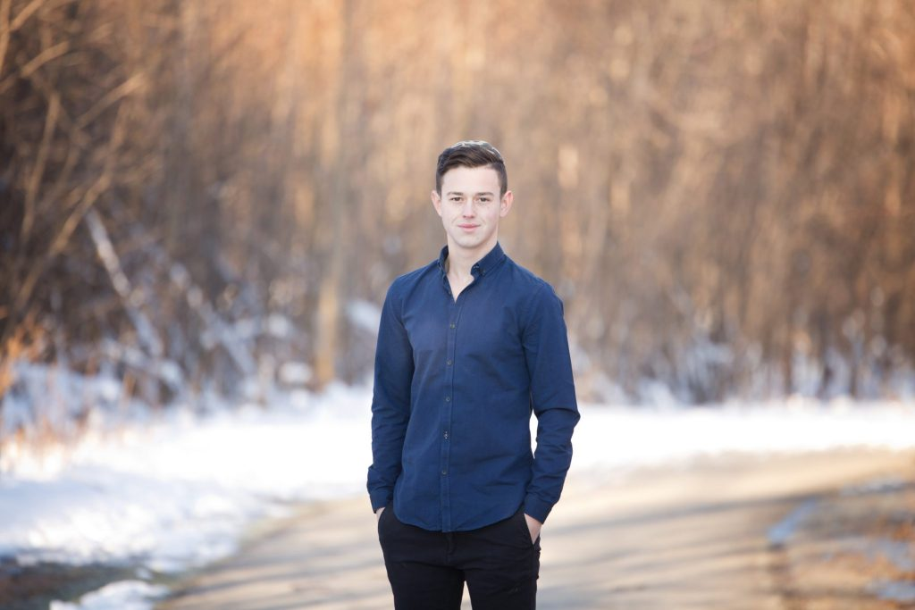 tall dry grass and snow behind young man in blue shirt as he poses for his senior session