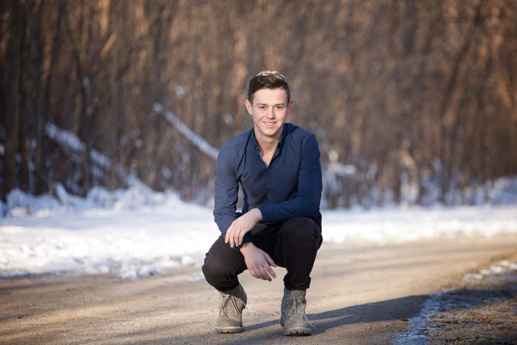 high school senior crouches down to pose on a path in beachwood