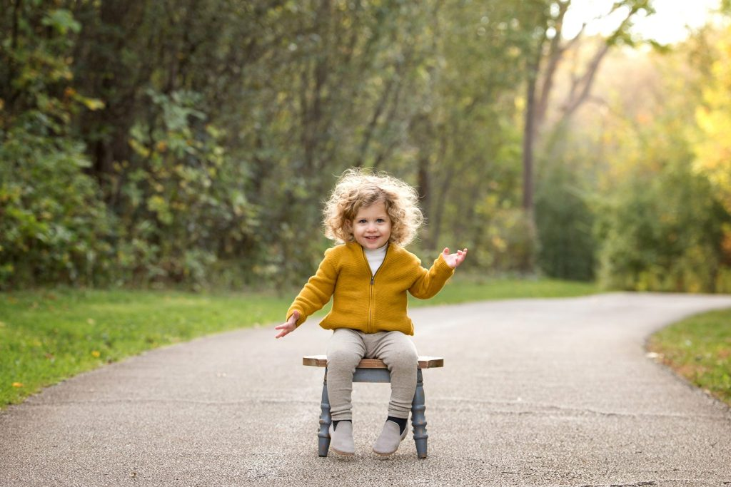 two year old boy with big blonde curls sits on a stool outside