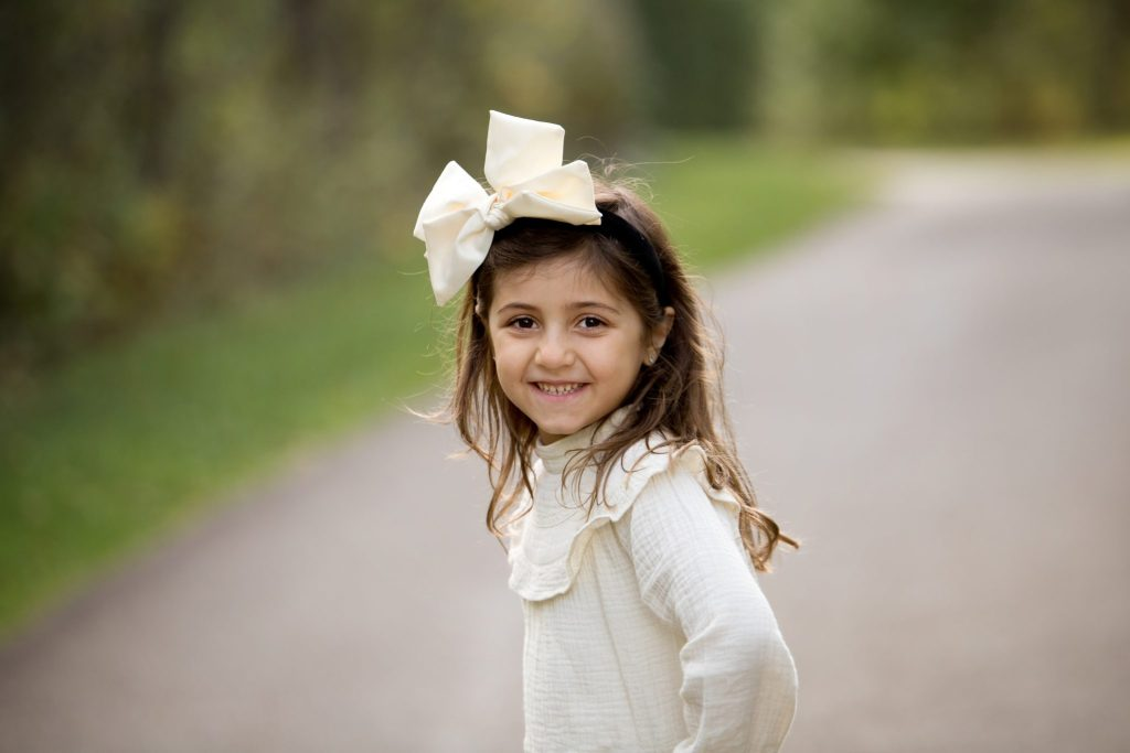 6 year old girl with a big cream colored bow in her hair poses outside
