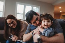 parents and little boy play in their family room