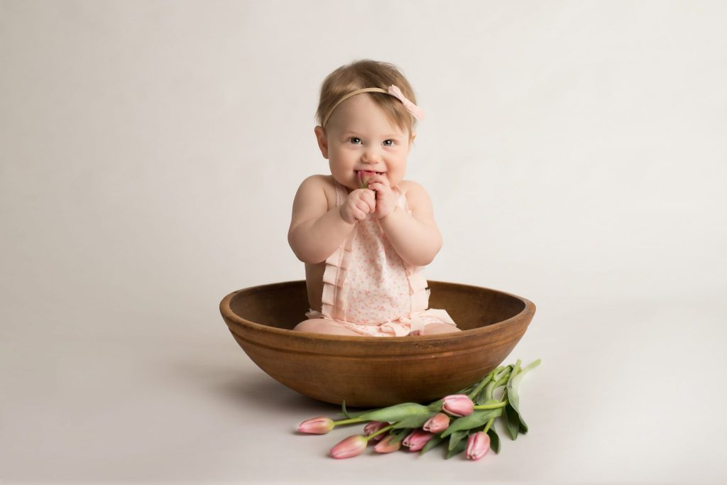 baby girl in a wooden bowl with tulips next to the bowl