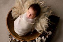 newborn baby boy in off white wrap in a wooden bowl