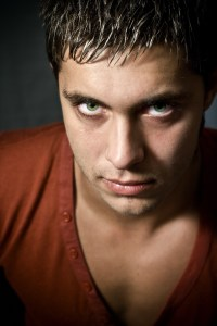 Low key portrait of intense looking guy with green eyes