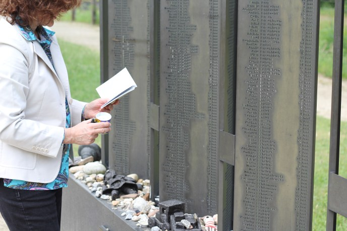 woman prays at memorial