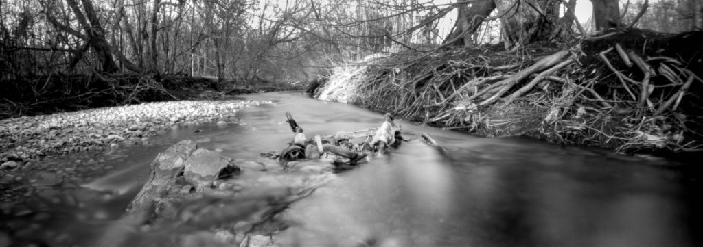 A black and white panoramic photo of a shopping cart submerged in a stream