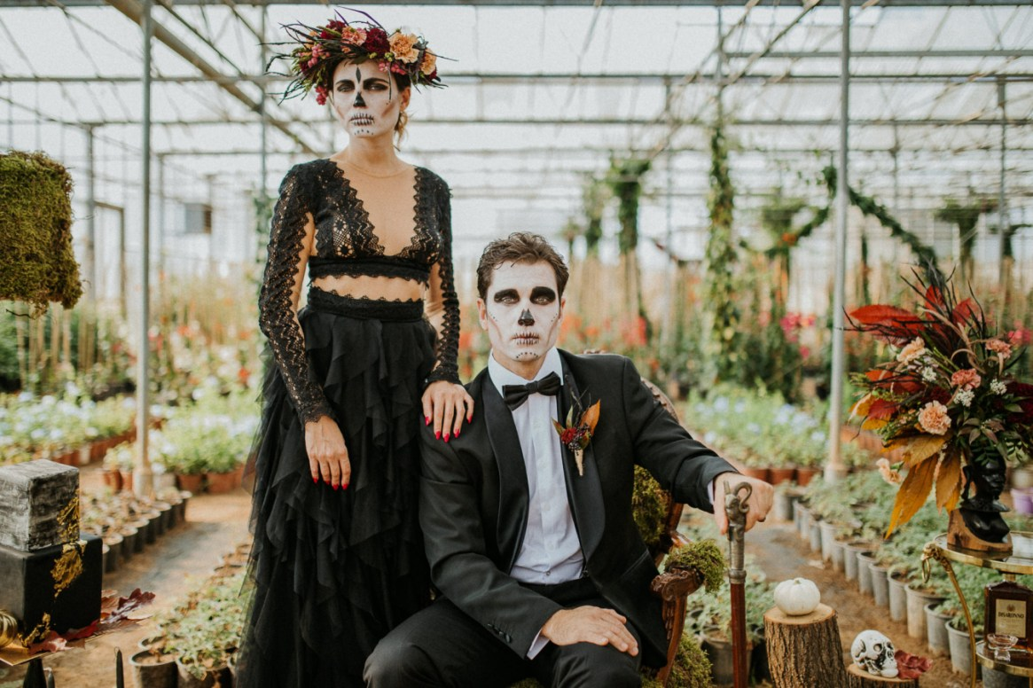Halloween Wedding couple groom and bride sitting in Greenhouse