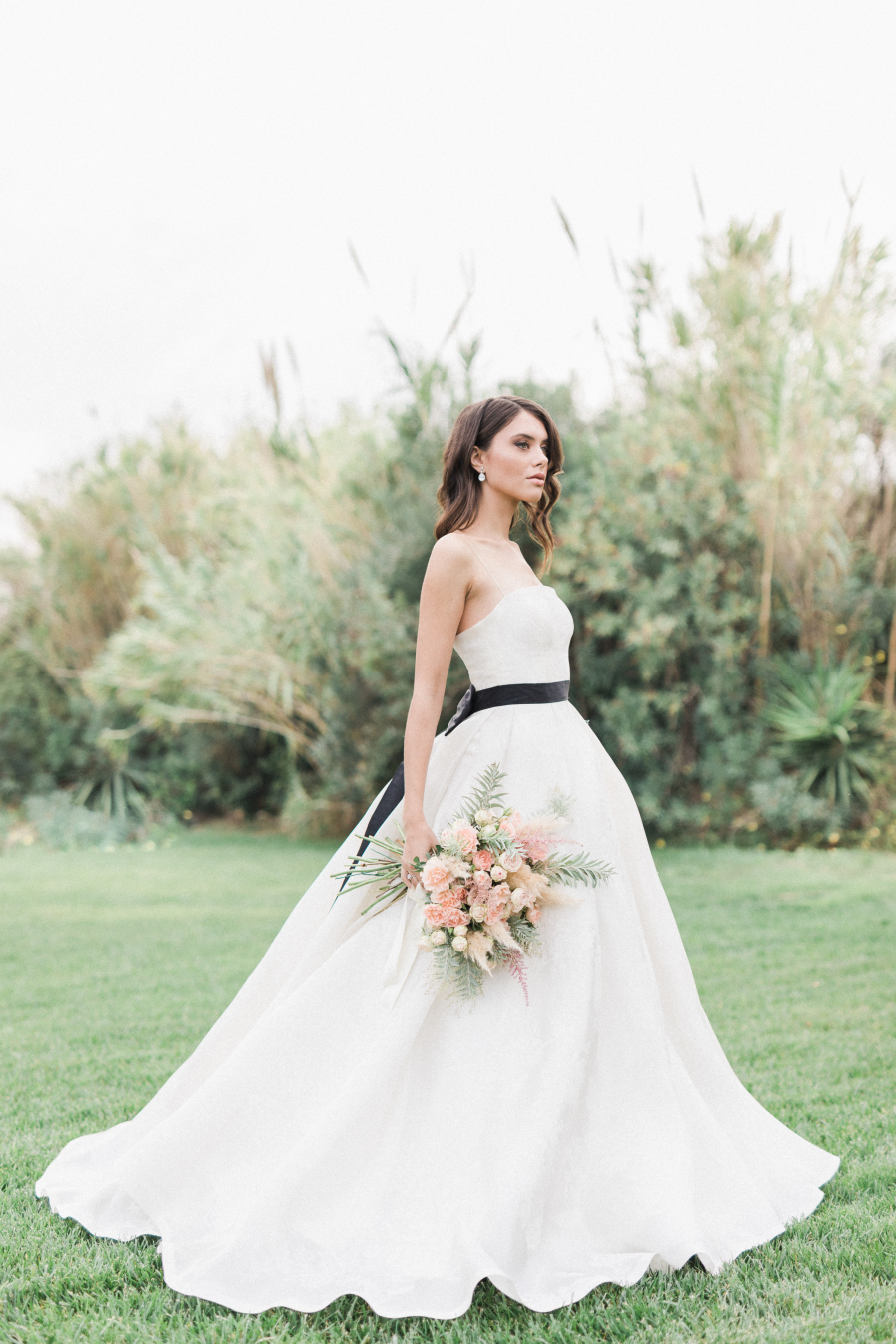 Bride with white dress and black belt holding a bridal bouquet