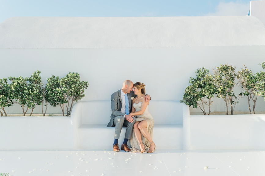 Hellenic Chic Elopement couple sitting on the white bench on the rooftop terrace on Santorini