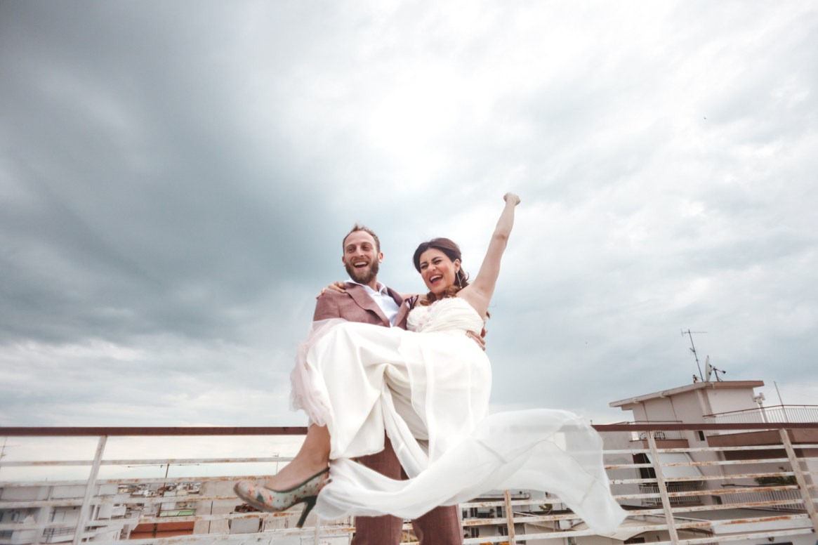 Happy Groom holding a happy Bride on the rooftop when they postpone their wedding