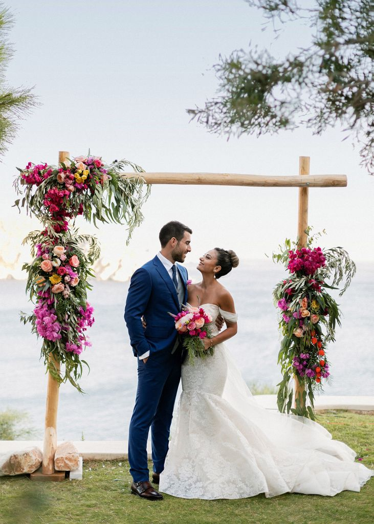 Afghan bride and Greek Groom standing under the ceremony arch for their Fun and colorful modern island wedding