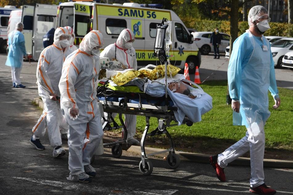 <strong><em>Los trabajadores médicos empujan una camilla que transporta a un paciente fuera del Hospital Scroff, oeste de Francia, en el sexto día de un bloqueo destinado a contener la propagación del nuevo coronavirus.</em></strong> (Foto de Fred TANNEAU / AFP)