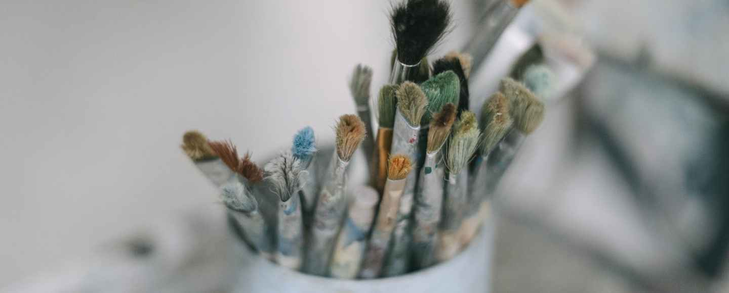paint brushes in a white container